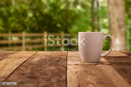 Composite image. Rustic, weathered wooden table with a white coffee cup on top of it.  Beautiful spring or summer background with a wooden fence. Sunny forest area, park, or backyard outdoor space. No people in this tranquil morning scene.