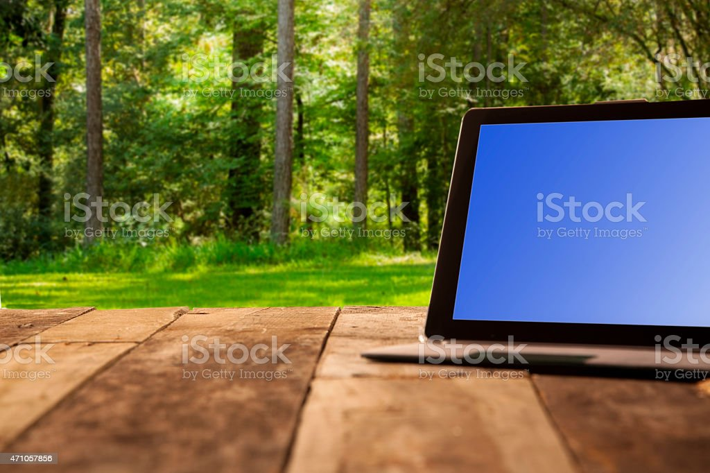 Spring or summer backyard background with digital tablet. Wooden table. stock photo