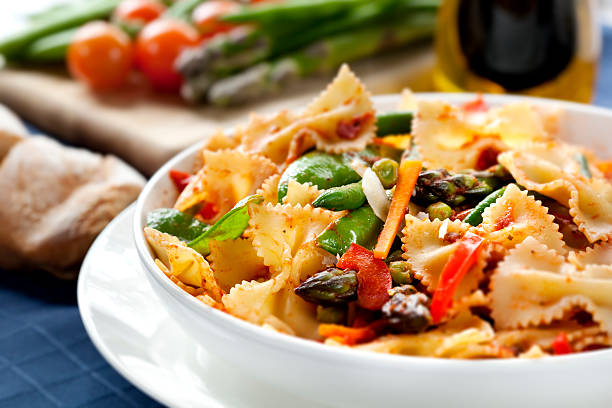 Pasta Primavera Pasta primavera.  Fresh bow-tie pasta with asparagus, beans, peas, snow-peas, tomatoes, carrots and peppers. bow tie pasta stock pictures, royalty-free photos & images