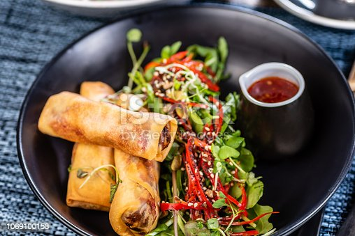 A plate of three spring rolls, green salad and chili sauce