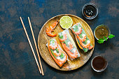Spring rolls with shrimp in rice paper with various sauces. Rustic blue rusty background. Top view, copy space