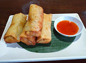 A typical Asian dish of vegetable spring rolls with sweet Thai chili sauce on a banana leaf