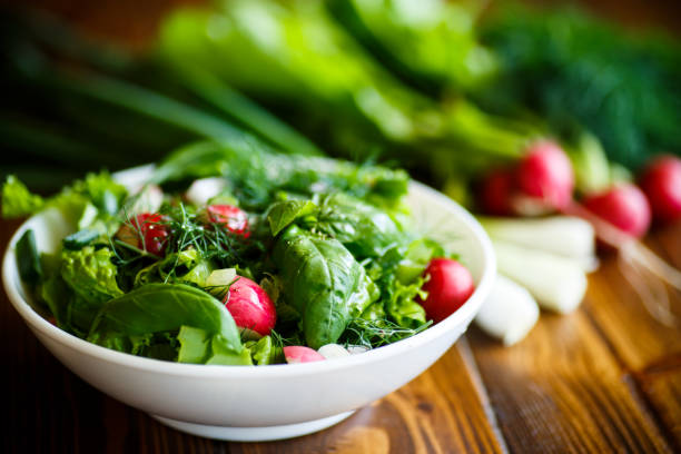 Spring salad from early vegetables, lettuce leaves, radishes and herbs stock photo