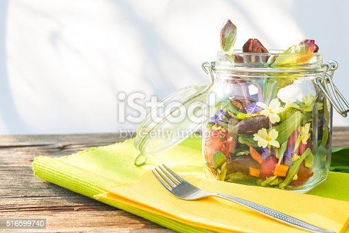 Yellow and purple primrose, lettuce, radicchio, cherry tomatoes, carrots, radish in glass bowl green cloth and on old wooden background and fork.