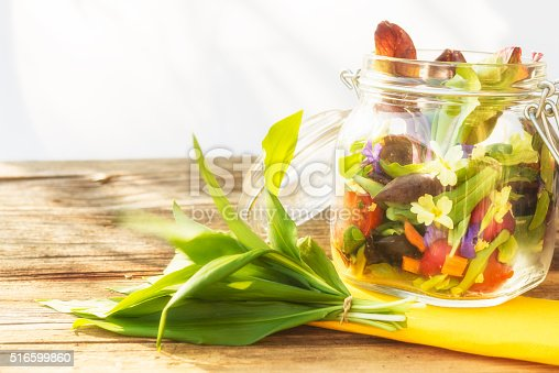 Yellow and purple primrose, lettuce, radicchio, cherry tomatoes, ramson, carrots, radish in glass bowl on old wooden background.
