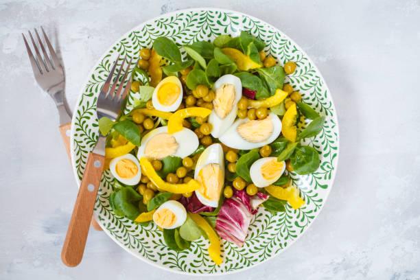 frühlings-salat mit huhn und wachteleier, kopfsalat, mais, paprika. ansicht von oben - englischer erbsen salat stock-fotos und bilder