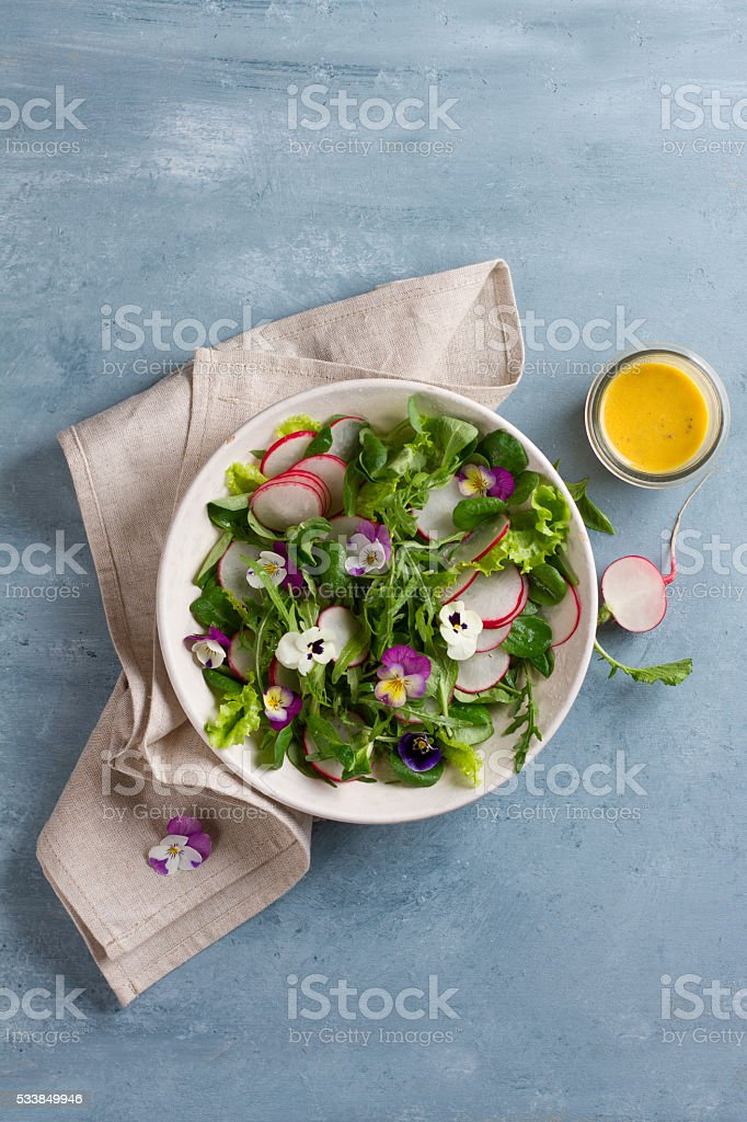 Spring salad with radishes, edible flower and sauce stock photo