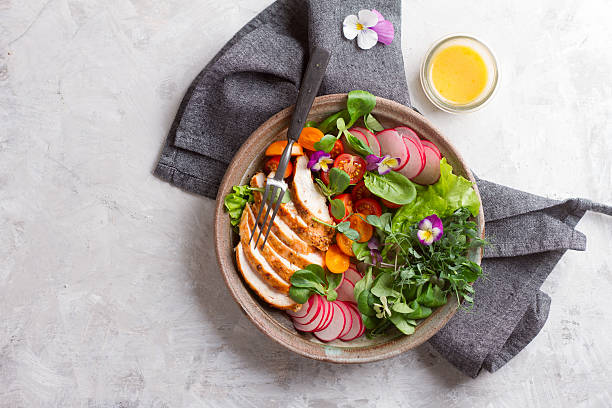 spring salad with vegetables, chicken breast and edible flowe - saladier photos et images de collection