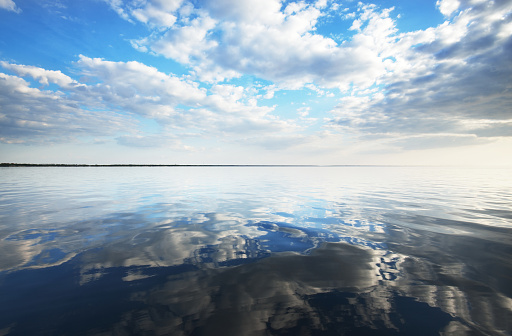 Spring seascape. The calm water. Beautiful colorful sunset over the Baltic Sea. White clouds. Latvia