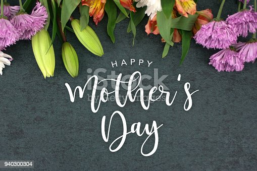 istock Spring season still life with Happy Mother's Day greeting holiday script over dark blackboard background 940300304