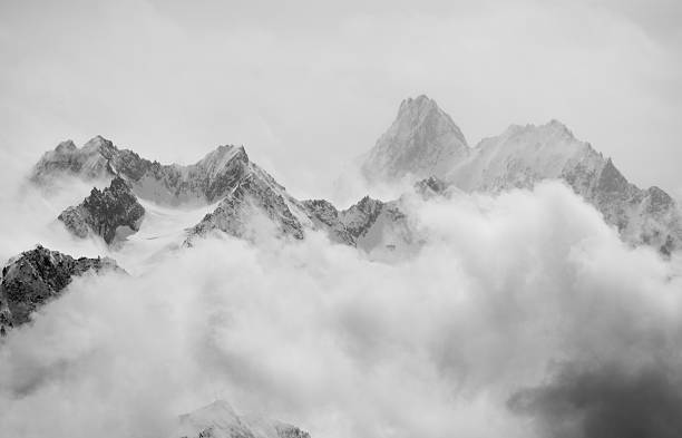 Spring snow showers in the alps Atmospheric clouds linger around the peaks of the Swiss alps after a spring snow storm. monochrome stock pictures, royalty-free photos & images