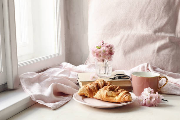 spring still life scene. cup of coffee, croissant pastry, old books and scissors. vintage feminine styled photo. floral composition with pink sakura, cherry tree blossoms on white table near window. - cherry blossoms imagens e fotografias de stock