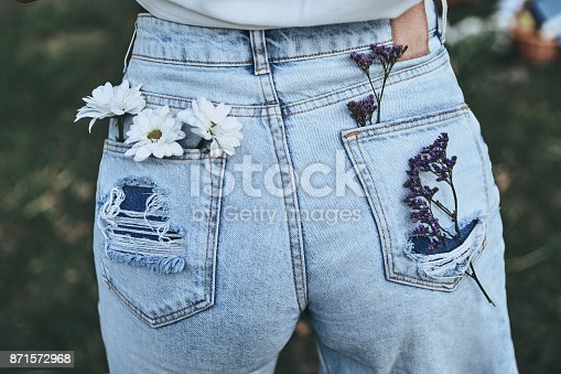 Close-up rear view of woman keeping chamomile and lavender in back pockets of her blue jeans while standing outdoors