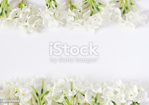 istock Spring styled stock photo. Easter concept. Feminine desktop scene. Frame of narcissus, daffodil flowers on white table background. Empty space. Flat lay, top view 931474944