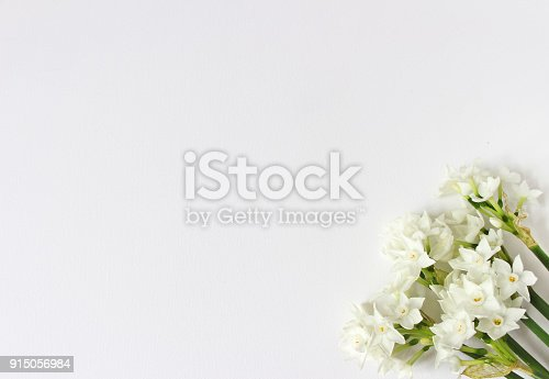 istock Spring styled stock photo. Easter concept. Feminine desktop scene with bouquet of narcissus, daffodil flowers on white table background. Empty space. Flat lay, top view 915056984