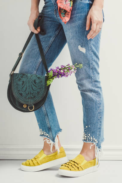 spring summer fashion jeans and yellow shoes and flowers stock photo