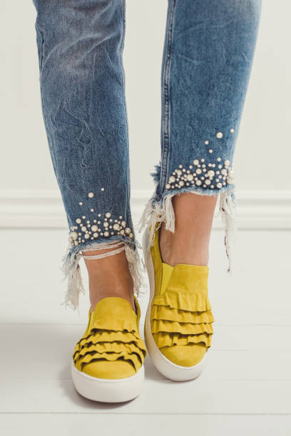 spring summer fashion jeans and yellow shoes foot and legs stock photo