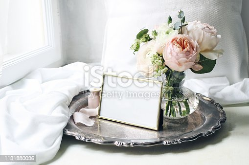 Spring, summer still life scene. Blank golden photo frame old silver tray at windowsill. Vintage feminine styled photo. Floral composition, bouquet of pink English roses, Ranunculus and eucalyptus.