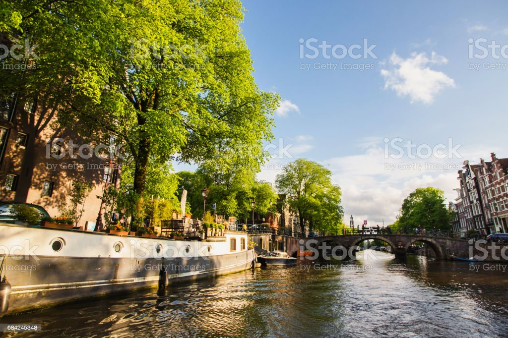 Spring sunny Amsterdam. The bright clear blue sky with white clouds. Boat trip on the canals of Amsterdam. The bridge over the water. Travel to Europe royalty-free stock photo