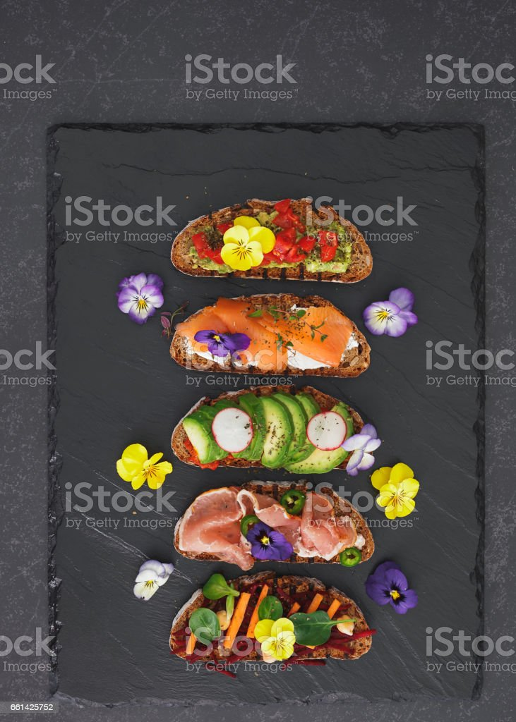 Spring tea sandwiches with flowers and herbs stock photo