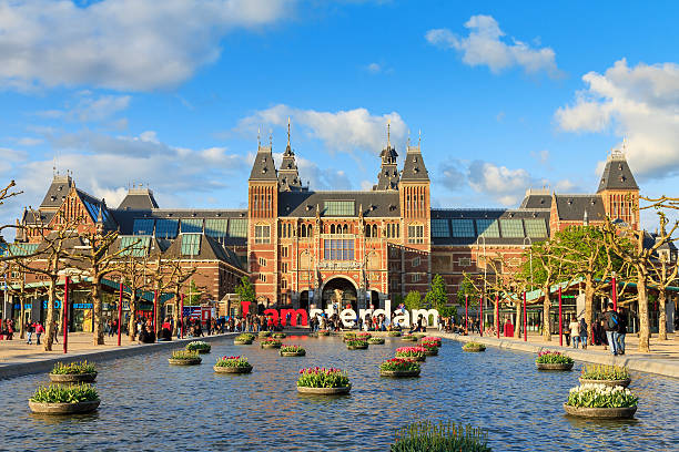 Spring tourism Amsterdam Amsterdam, The Netherlands - May 2, 2014: Beautiful vibrant spring view of tourists at the Rijksmuseum in Amsterdam on May 2, 2014 museumplein stock pictures, royalty-free photos & images