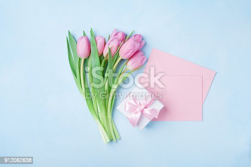 istock Spring tulip flowers, gift box and pink paper card on blue pastel table top view. Greeting for Womans or Mothers Day. 912062638