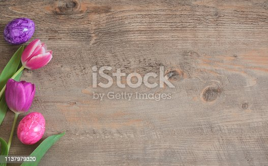 Spring Tulips and Easter Eggs on wooden background