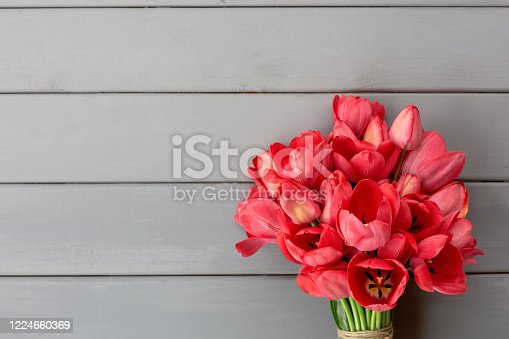 921112244 istock photo Spring tulips bouquet on grey wooden background. Flat lay. Copy space 1224660369