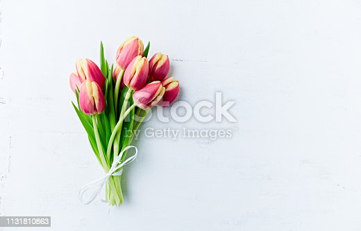 Spring tulips on white painted wooden background. Flat lay. Copy space