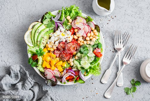istock Spring vegetable salad with chickpeas, avocado and feta. Tasty healthy food. Buddha bowl. On a gray background, top view 656873394