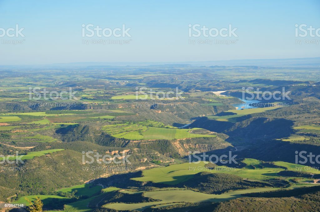 Spring view of the Spanish plain with a river in the canyon, Hoya de Huesca stock photo