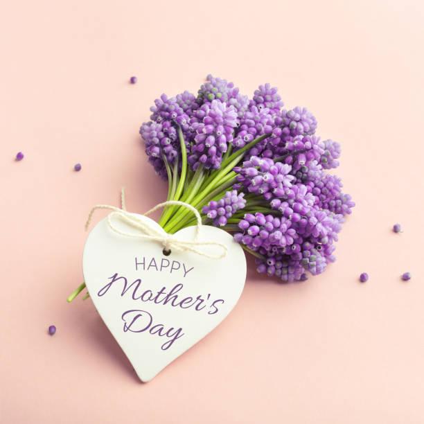 Frühlingsgrümmblumen und eine Herzform Karte Happy Mother es Day auf Pastellrosa. – Foto