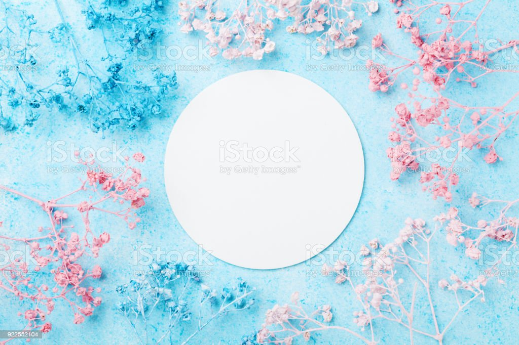 Spring Woman day card. Wedding mockup with white paper list and flowers on blue punchy pastel table top view. Beautiful floral pattern. stock photo