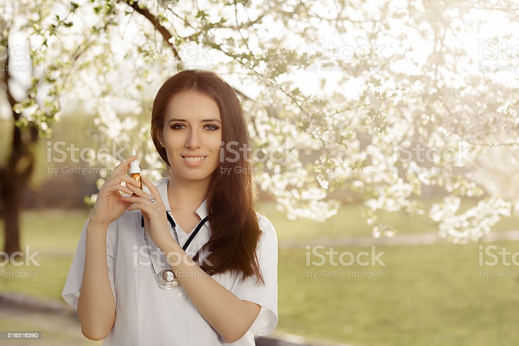 Spring Woman Doctor Smiling and Holding Respiratory Spray stock photo