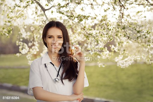 istock Spring Woman Doctor Smiling and Holding Respiratory Spray 516316394
