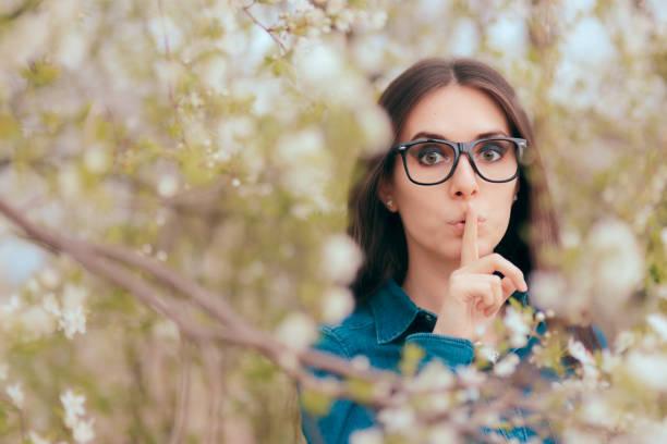 frühling-frau trägt brille halten ein geheimnis in der blühenden natur - wahre lügen stock-fotos und bilder