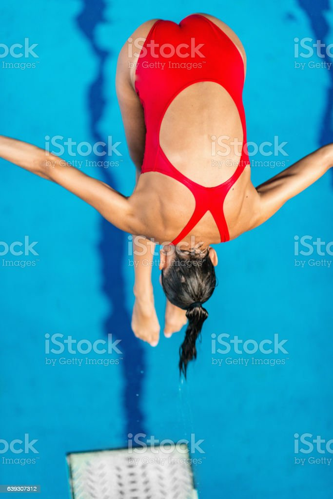Springboard diver, jumping into the pool stock photo