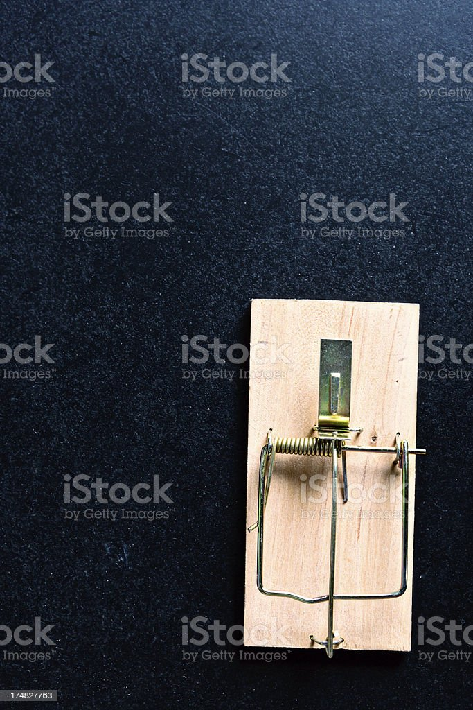 Springing the trap: mousetrap ready for action against black stock photo