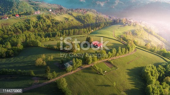 Romanian rural landscape scene, fences and cottages, tiny winding roads, pastures and farmlands, drone point of view