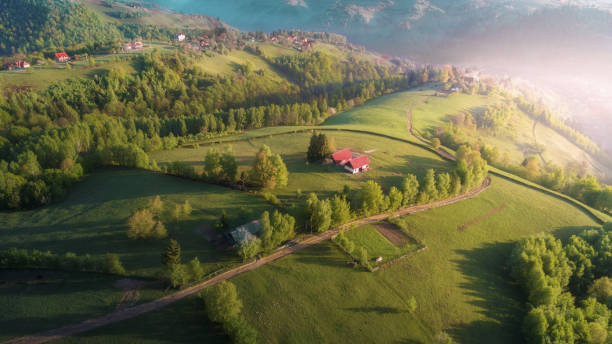 Springtime. Aerial view over Transylvania green fields, mountain village at sunrise, bright sunlight, small houses, springtime, greenery, Carpathian mountains, majestic view, travel destinations Romanian rural landscape scene, fences and cottages, tiny winding roads, pastures and farmlands, drone point of view romania stock pictures, royalty-free photos & images
