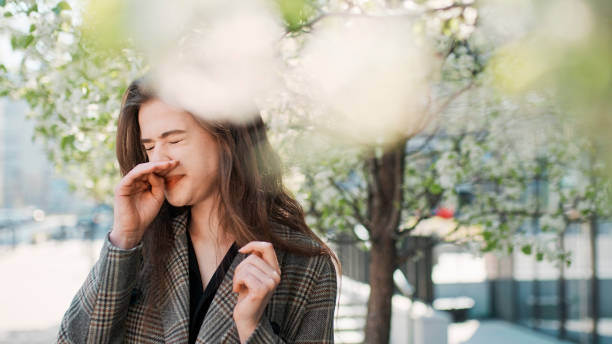 Springtime allergy. Woman sneezing on the city street stock photo