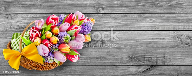 istock Springtime flowers and basket on wooden background 1127283682