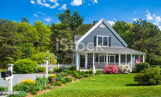 An American flag flies from the open porch and gardens surround a small  single family home on a Spring afternoon on Cape Cod on the Massachusetts coast.