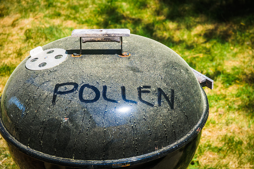 A backyard domed charcoal barbeque grill with a thick coating of green pine pollen on top and the word \