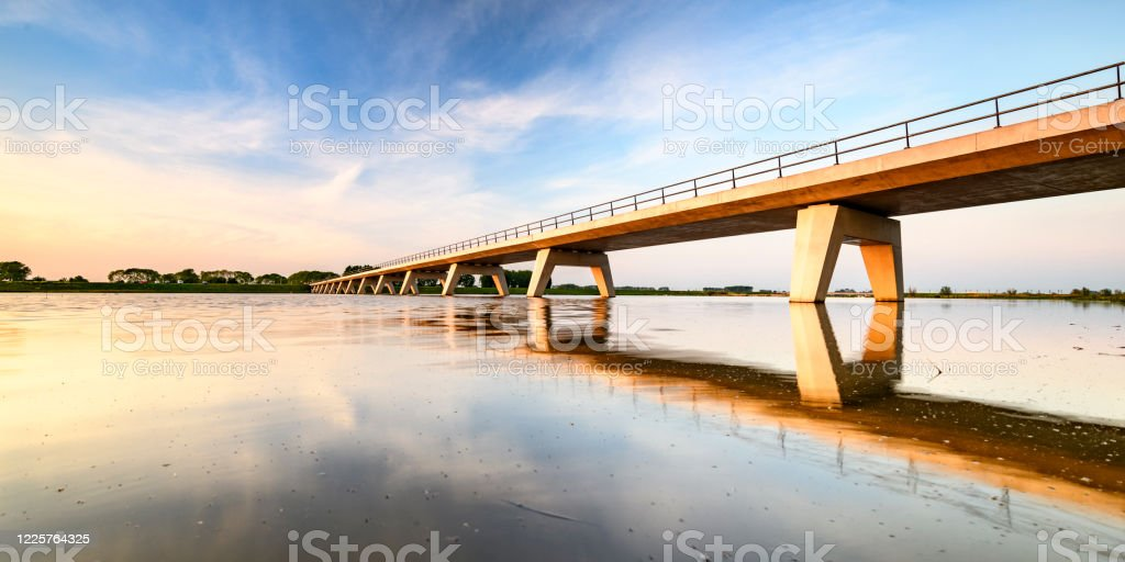 Springtime sunset over a bridge over a lake during a beautiful evening in May Springtime sunset over a bridge over the Reevediep lake during a beautiful evening in May near Kampen in Overijssel, The Netherlands. Bridge - Built Structure Stock Photo