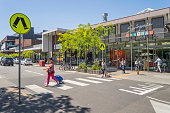 Melbourne, Australia - November 14, 2017: A woman with a shopping trolley bag crosses a pedestrian crossing in Springvale, while other shoppers are seen outside the entrance to the Springvale Central shopping centre. The suburb is home to a large Vietnamese community.
