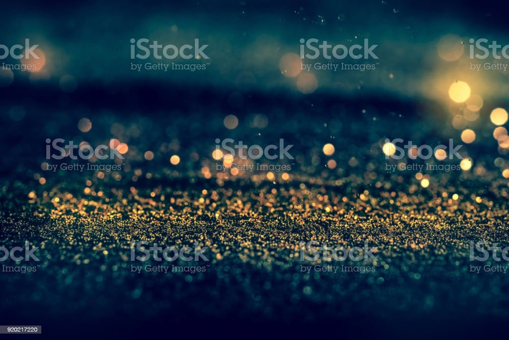 Sprinkle glitter gold dust in the dark with copy space stock photo