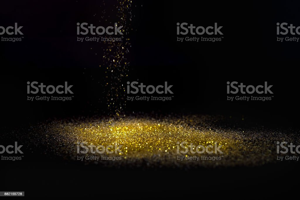 Sprinkle glitter gold dust on a black background with copy space stock photo