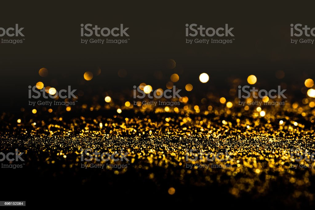 Sprinkle gold dust on a black background in the dark stock photo