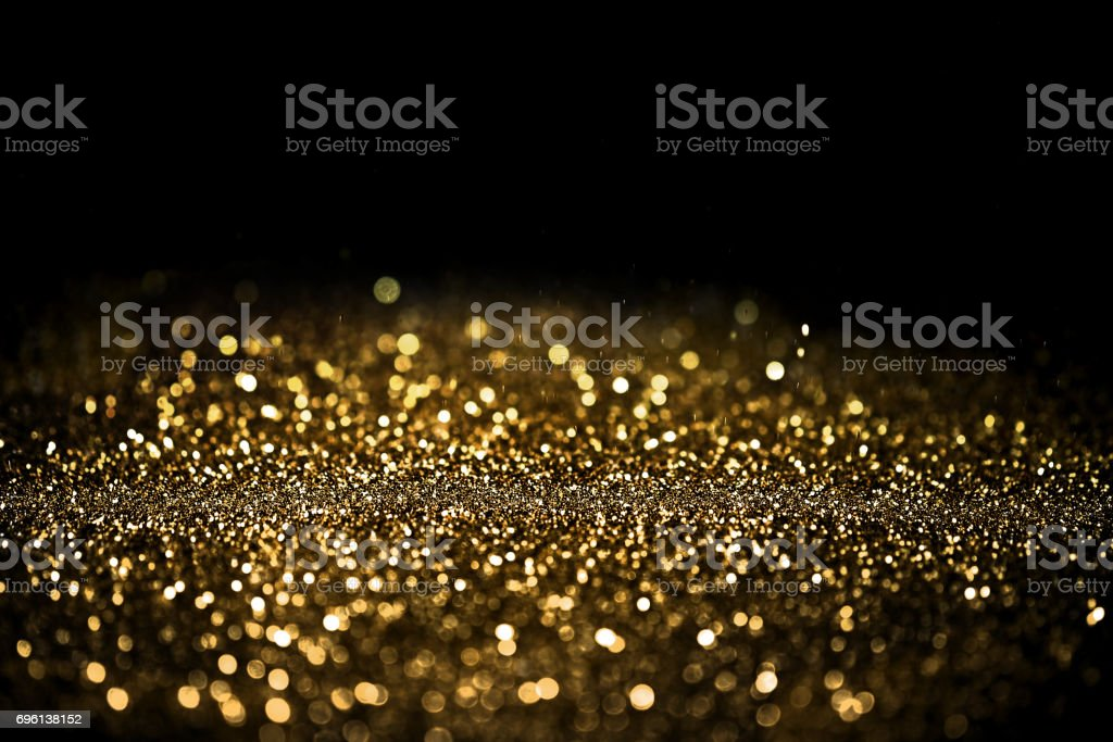 Sprinkle gold dust on a black background with copy space stock photo